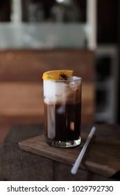 Ice black coffee with orange on wood background