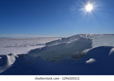 Ice blocks that have shifted off a frozen lake, in the background the frozen Fort Peck Lake in Montana with a clear blue sky and bright sunshine.