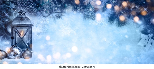 Ice blue christmas background with golden bokeh a burning lantern and christmas tree balls for a decoration