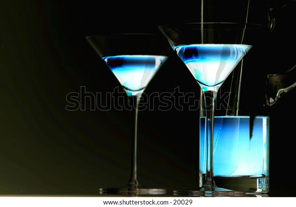 Ice blue cocktail in martini glasses. Pitcher included. Low key.