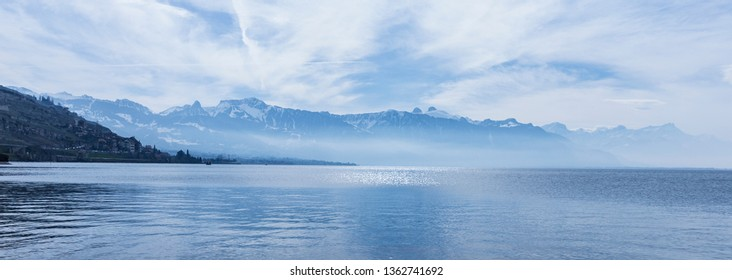 Ice blue nature skyline background of mountains and sea. Still water surface.of the Leman (Geneva) lake and the Alps, view from Switzerland in the morning
