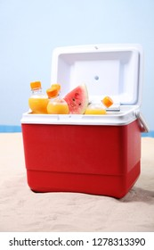 Ice box with orange juice bottles and water melon on white sand at the beach