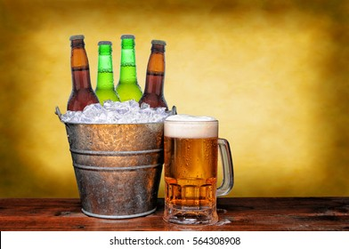 An ice bucket with three green beer bottles next to a full mug of ale on a wet wood surface. Horizontal format with warm mottled background.