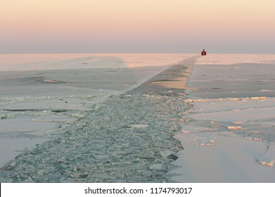 Ice canal made by icebreaker with red icebreaker visible on horizon.