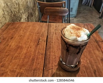 Ice Chocolate on wooden table in loft cafe style.