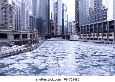 Ice chunks fill the Chicago River during winter. The ice floats through the city and the cityscape is in the background.