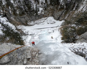 ice climber abseiling an ice fall in Italy