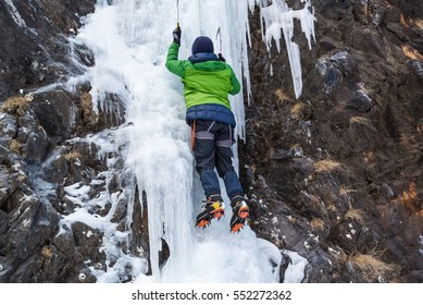 Ice climber in green jacket on steep frozen waterfall, top rope