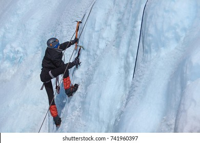 An ice climber makes his way up on a frozen waterfall