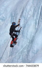An ice climber makes his way up on a frozen waterfall.