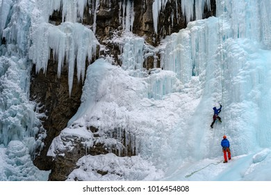 Ice climber on the frozen Upper Falls of the Johnston Creek during winter, Johnston Canyon, Banff National Park, Canadian Rocky Mountains, Alberta, Canada.