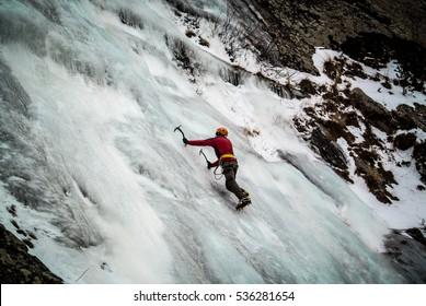 Ice climber on steep frozen waterfall