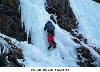 Ice climbers in a blue jacket and red pants on steep a frozen waterfall from the top rope