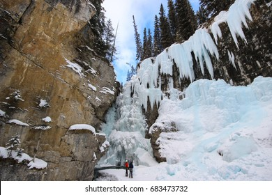 Ice climbers in front of a frozen waterfall in Johnston Canyon, Alberta, Canada