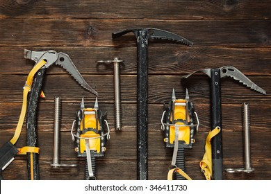 ice climbing equipment: ice tools, ice ax, ice screws, crampons on dark wooden background, top view. Travel concept.