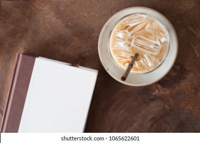 Ice coffee and book on wooden table , background