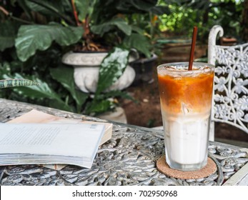ice coffee and books on white table in the garden