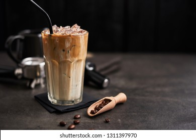 Ice coffee with cream in a tall glass and coffee beans, portafilter, tamper and milk jug on dark concrete table over black wooden background. Cold summer drink. Copy space for text. Selective focus.