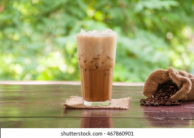 Ice coffee drink with sack of coffee beans on wooden table against green nature background