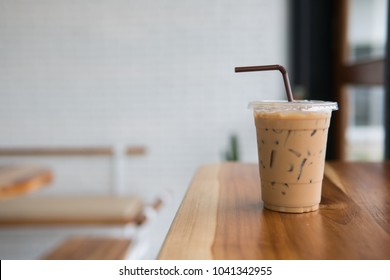 ice coffee with drinking straw on wooden table,ice coffee in take home glasses.