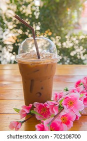 ice coffee in the glass, ice coffee on wood table over bokeh background.