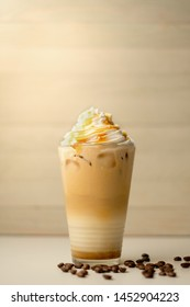 Ice coffee in the glass topped whipping cream with coffee beans. Cold summer drink on wooden background and copy space. Advertising for caramel mocha and chocolate beverage for the cafe.