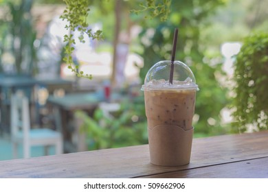 ice coffee to go in plastic cup  on table over blurred plantation of coffee tree with sun lighting.sunset colors