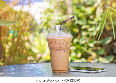 ice coffee to go with smartphone on table in garden