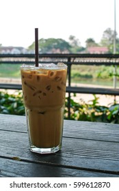 ice coffee in high glass on wooden table