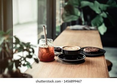 Ice coffee and latte art on wooden table coffee shop background