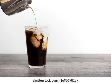 Ice coffee latte with cream being poured into it showing the texture and refreshing look of the drink, with a clean background.