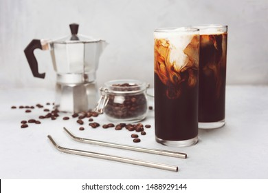 Ice coffee, mocha coffee maker, metal straws on trendy background. Cold summer drinks and refreshment concept.