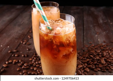 Ice coffee on a rustic table with cream being poured into it showing the texture and refreshing look of the drink.