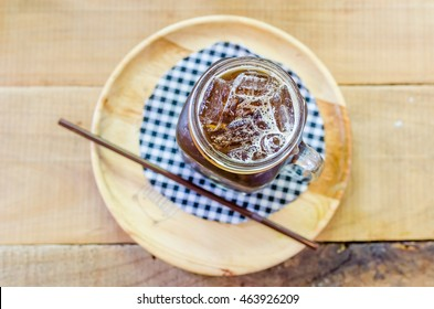 Ice coffee on tablecloth on wood plate on wood table, top view. Selective focus