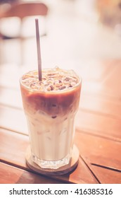 Ice coffee on wood table background. Shallow dept of field. Drink background concept. Retro color style.