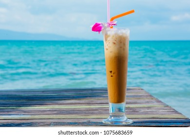 Ice coffee on wooden table with blue sea background