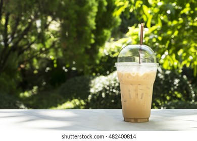 Ice coffee in plastic cup at the park.
