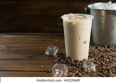 Ice coffee in plastic glass, bucket with ice, coffee seeds and ice cubes on wooden background