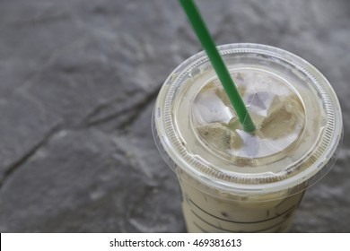 ice coffee in plastic glass with green straw on granite background