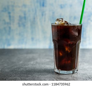 Ice coffee in a tall glass  Cold summer drink on a gray background with copy space.