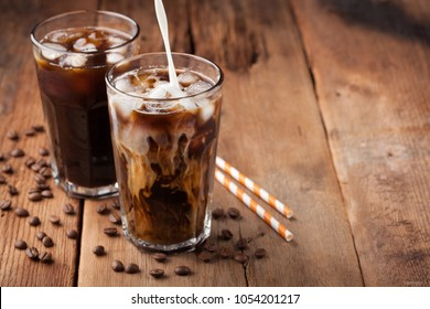 Ice coffee in a tall glass with cream poured over and coffee beans on a old rustic wooden table. Cold summer drink on a dark wooden background with copy space