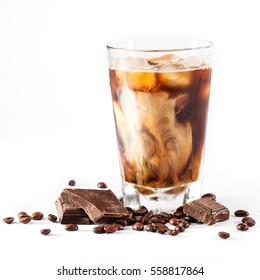 ice coffee in a tall glass with cream and coffee beans, pieces of chocolate on a white background