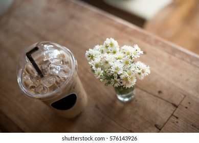 Ice coffee with white flower on wood table