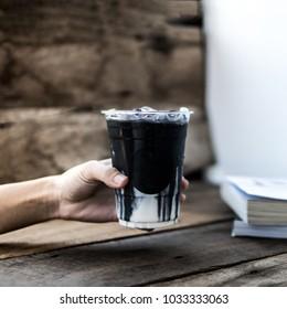 ice coffee,charcoal latte coffee,hand holding coffee.