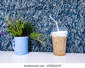 Ice coffeee and vase of flower bouqute on table and blue & white yarn background. Concept of coffee time.
