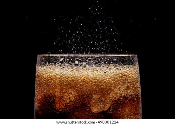 Ice cola with splashing CO bubbles. Drink with ice, closeup, fizzing, fizz.