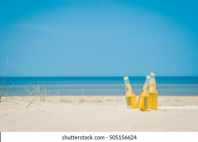 Ice cold beer bottles in the sand under the bright sun