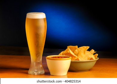 Ice cold beer with chips and salsa with a blue splash background