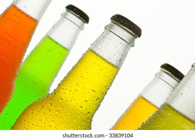 A lot of ice cold bottles with fresh tropical drinks