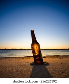 Ice cold brown bottle of beer / soda standing upright in the golden sand. Summer evening
